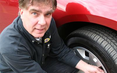 Bill Gardiner Checking Tire Pressure - Photo by Matthew Haase, Edmonton Journal